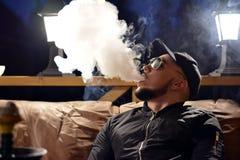 Porträt eines jungen Mannes, der Rauch ausatmet Stockfotos