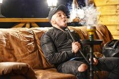 Porträt eines jungen Mannes, der Rauch ausatmet Lizenzfreies Stockbild