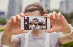 Porträt eines jungen Mannes, der selfie auf dem Hintergrund der Stadt macht Stockfotografie