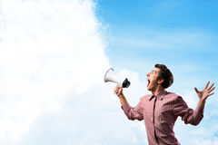 Porträt eines jungen Mannes, der unter Verwendung des Megaphons schreit Stockfotos