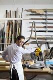 Porträt eines jungen Mannes, der zurück schaut, bei der Anwendung des Rundschreibens sah in der Werkstatt Lizenzfreie Stockbilder