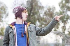 Porträt eines jungen Mannes mit einem Hut seinen Finger zeigend Stockfotografie