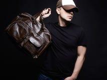 Porträt eines jungen Mannes mit Handtasche Stockfotografie