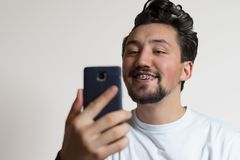 Porträt eines jungen Mannes mit Klammern lächelnd und einen Smartphone betrachtend Ein glücklicher junger Mann, der seine Klammer lizenzfreies stockfoto