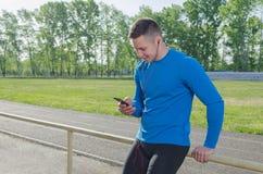 Porträt eines jungen muskulösen Sportlers, der Musik nach einem Training hört stockbild
