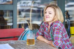 Porträt eines jungen netten lächelnden Mädchens, das in einem Café mit einem Becher Bier sitzt stockfotografie