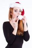 Porträt eines jungen netten rothaarigen Mädchens in einem glänzenden Weihnachtshut Lizenzfreie Stockbilder