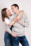 Porträt eines jungen Paares, das gegen Hintergrund des blauen Graus steht Stockfotos