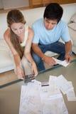 Porträt eines jungen Paares, das ihre Rechnungen betrachtet Stockfotos