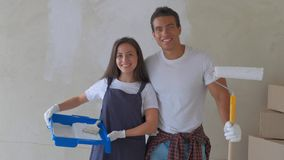 Porträt eines jungen Paares in einem neuen Haus sind, verzierend malend und die Wand ihres Hauses stock footage