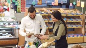 Porträt eines jungen Paares mit einer vollen Laufkatze von Produkten im Supermarkt stock footage