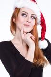 Porträt eines jungen reizend rothaarigen Mädchens in einem glänzenden Weihnachtshut Stockfotos