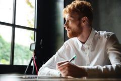 Porträt eines jungen Rothaarigemannschreibens in einem Notizbuch Lizenzfreie Stockfotografie