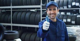 Porträt eines jungen schönen Automechanikers in einer Autowerkstatt, im Hintergrund einer Autoservicekonzeptreparatur der Maschin lizenzfreie stockfotos