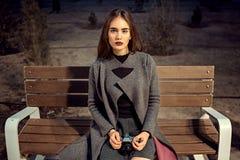 Porträt eines jungen schönen brunette Mädchens in einem grauen Mantel und in Burgunder-Strümpfen, die auf einer Bank mit einer We stockfotografie