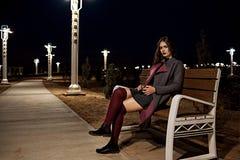 Porträt eines jungen schönen brunette Mädchens in einem grauen Mantel und in Burgunder-Strümpfen, die auf einer Bank mit einer We stockbilder