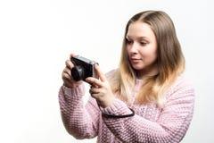 Porträt eines jungen schönen glücklichen Mädchentragens blaß - zacken Sie die gestrickte Strickjacke aus, die eine Weinlesekamera Lizenzfreie Stockfotografie