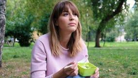 Porträt eines jungen schönen Mädchens, das einen vegetarischen Salat isst Studentin essen am Park zu Mittag Gewichtverlust Frauen stock video footage