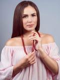 Porträt eines jungen schönen Mädchens, das Halskette hält stockfotografie