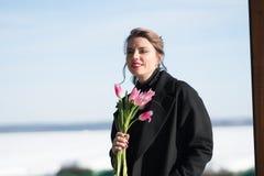 Porträt eines jungen schönen Mädchens in der Straße im Winter in einem schwarzen Mantel lizenzfreies stockbild