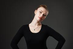 Porträt eines jungen schönen Mädchens im Schwarzen auf einem grauen Hintergrund lizenzfreies stockbild