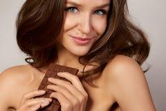 Porträt eines jungen schönen Mädchens mit dem dunklen gelockten Haar, bloße Schultern, die einen Schokoriegel halten, um den Gesc Stockfoto