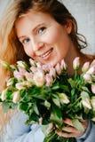 Porträt eines jungen schönen Mädchens mit einem Blumenstrauß von Rosen nahe Fenster stockfoto