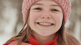 Porträt eines jungen Schulmädchens mit Sommersprossen im Wald im Winter Das Mädchen berührt ihre Nase mit ihrer Hand in stock footage