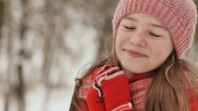 Porträt eines jungen Schulmädchens mit Sommersprossen im Wald im Winter Er wärmt seine Hände in den Handschuhen und wendet sie an stock footage