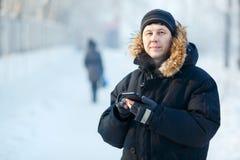Porträt eines jungen sibirischen Mannes mit Telefon in den Händen, tragende warme unten Jacke, Pelzhaube Kalter Wintertag Stockfotos