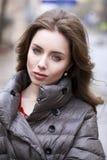 Porträt eines jungen stilvollen Brunettemädchens in einer des Graus Jacke unten Stockfotografie
