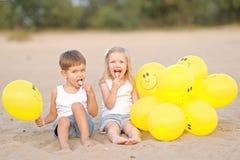 Porträt eines Jungen und des Mädchens auf dem Strand Stockfotografie