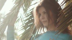 Porträt eines jungen und schönen Modells, das nahe Palmen im Park aufwirft stock video