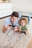 Porträt eines Jungen und seines Vaters, die Videospiele spielen stockfoto