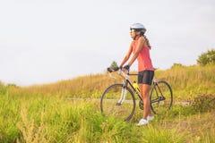 Porträt eines jungen weiblichen Sportathleten mit laufendem Fahrrad restin Lizenzfreies Stockbild