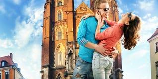 Porträt eines küssenden Paares, das herein in die Stadt stillsteht lizenzfreie stockbilder