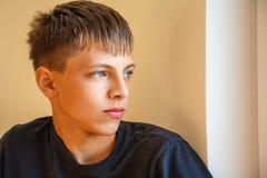 Porträt eines Kerls, der heraus das Fenster schaut stockfotos