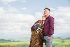 Porträt eines Kerls mit einem Mädchen bedeckt in einer Decke, die in einer Umarmung in der Natur steht und mit Glück lächelt Stockbild