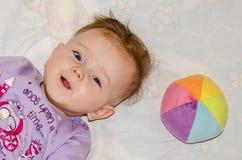 Porträt eines kleinen Babys, das mit einem Ball und einem Lächeln liegt Lizenzfreie Stockfotografie