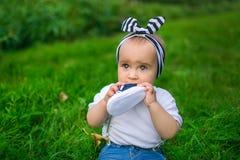 Porträt eines kleinen Babys kaut seinen Schuh auf einem Gras stockfotos