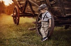 Porträt eines kleinen Herrn, der auf einem alten Wagen sich lehnt stockbilder