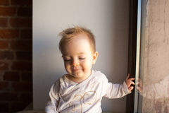 Porträt eines kleinen Jungen, der im Fenster und im Lächeln sitzt Gefühlkonzept Lizenzfreie Stockfotografie