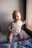 Porträt eines kleinen Jungen, der im Fenster und im Lächeln sitzt Gefühlkonzept Stockfotografie
