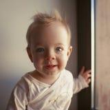 Porträt eines kleinen Jungen, der im Fenster und im Lächeln sitzt Gefühlkonzept Lizenzfreies Stockfoto