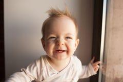 Porträt eines kleinen Jungen, der im Fenster und im Lächeln sitzt Gefühlkonzept Stockbild