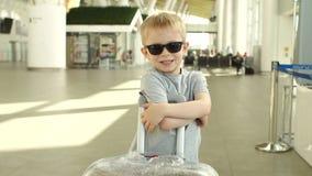 Porträt eines kleinen Jungen in der Sonnenbrille mit einem Koffer am Flughafen stock video