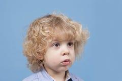 Porträt eines kleinen Jungen mit dem blonden gelockten Haar Lizenzfreies Stockfoto