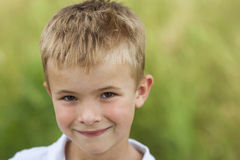 Porträt eines kleinen lächelnden Jungen mit goldenem blondem Strohhaar I Stockfotografie