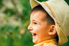 Porträt eines kleinen lachenden glücklichen Jungen in einem Hut von der Sonne im Garten Lizenzfreies Stockfoto