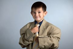 Porträt eines kleinen lustigen Jungen in Vati ` s großer Klage: eine Jacke und eine Bindung lizenzfreie stockfotografie